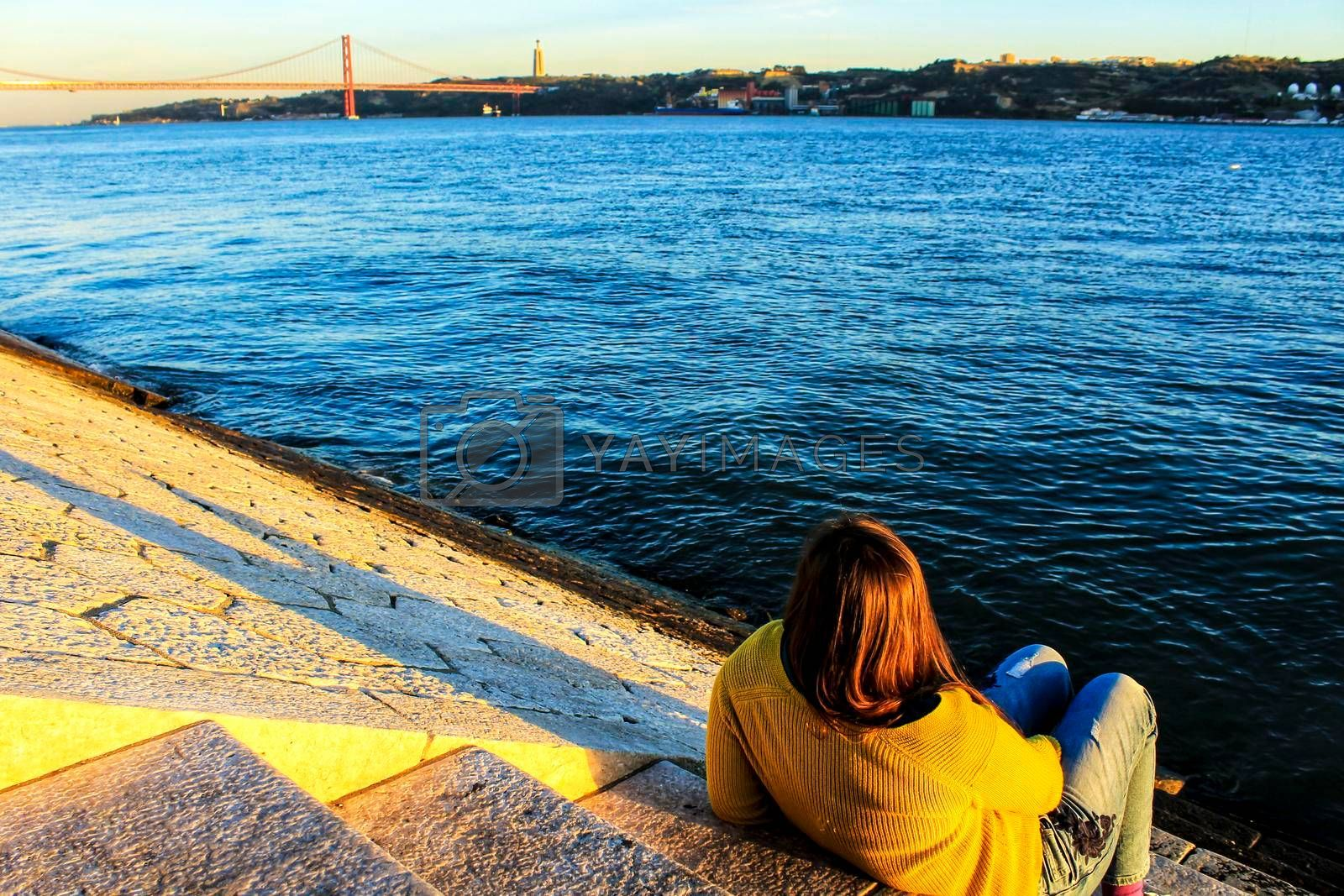 Girl sitting next to the riverbank at sunset in Lisbon, Portugal