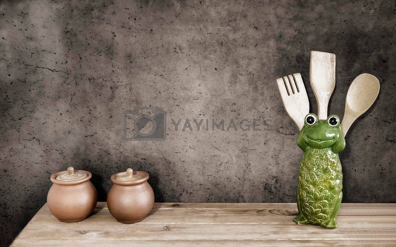 On the kitchen shelf are wooden cooking utensils and dishes. Front view, copy space