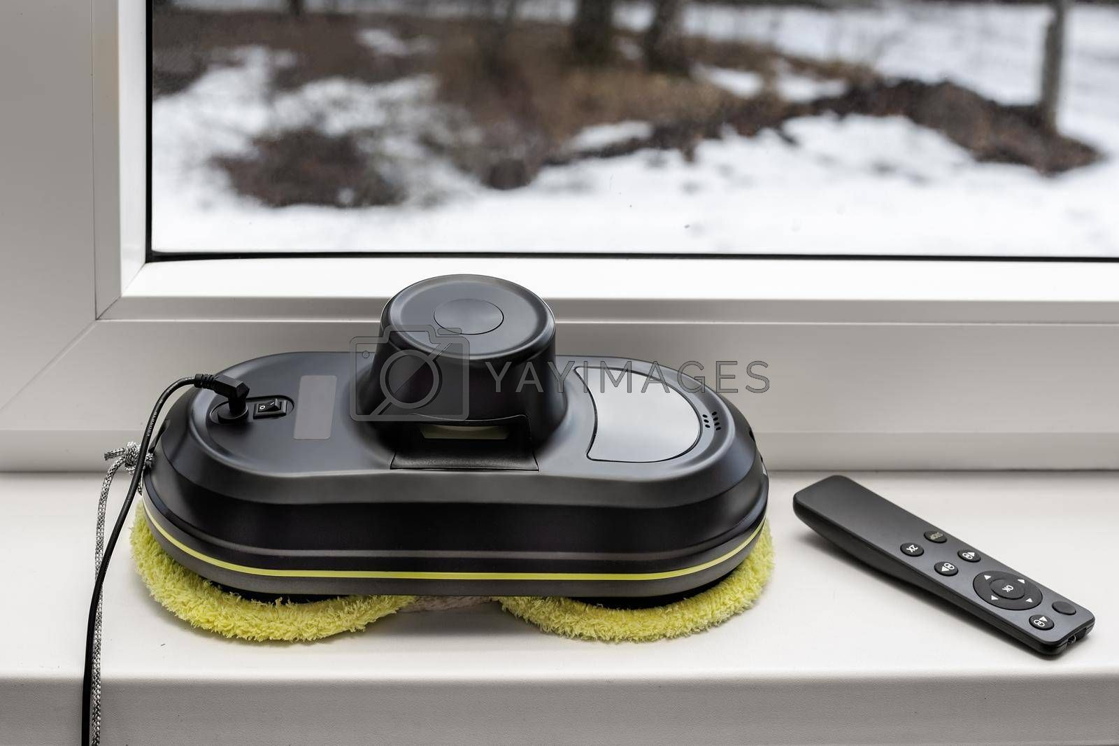 Robotics, a window cleaner robot and a remote control for cleaning window panes. Lying on the windowsill. Front view . Copy space