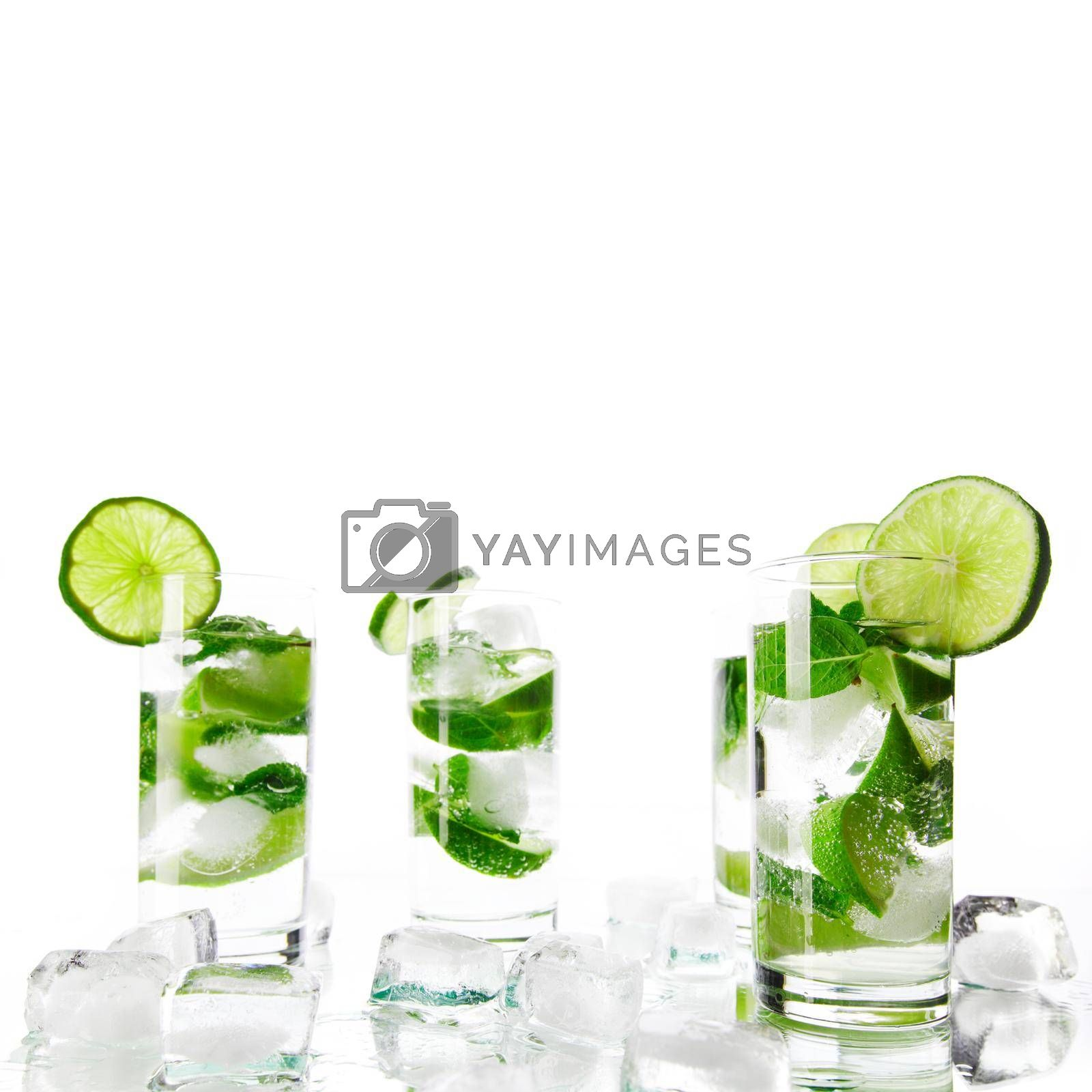 Party mojito cocktails with lime and mint ice cubes isolated on white background