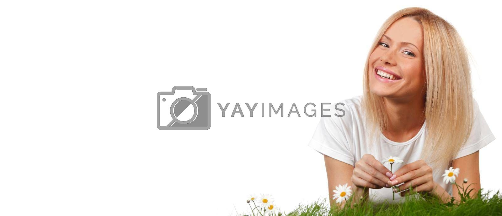 Happy young woman lying on grass with chamomile flowers, isolated on white background