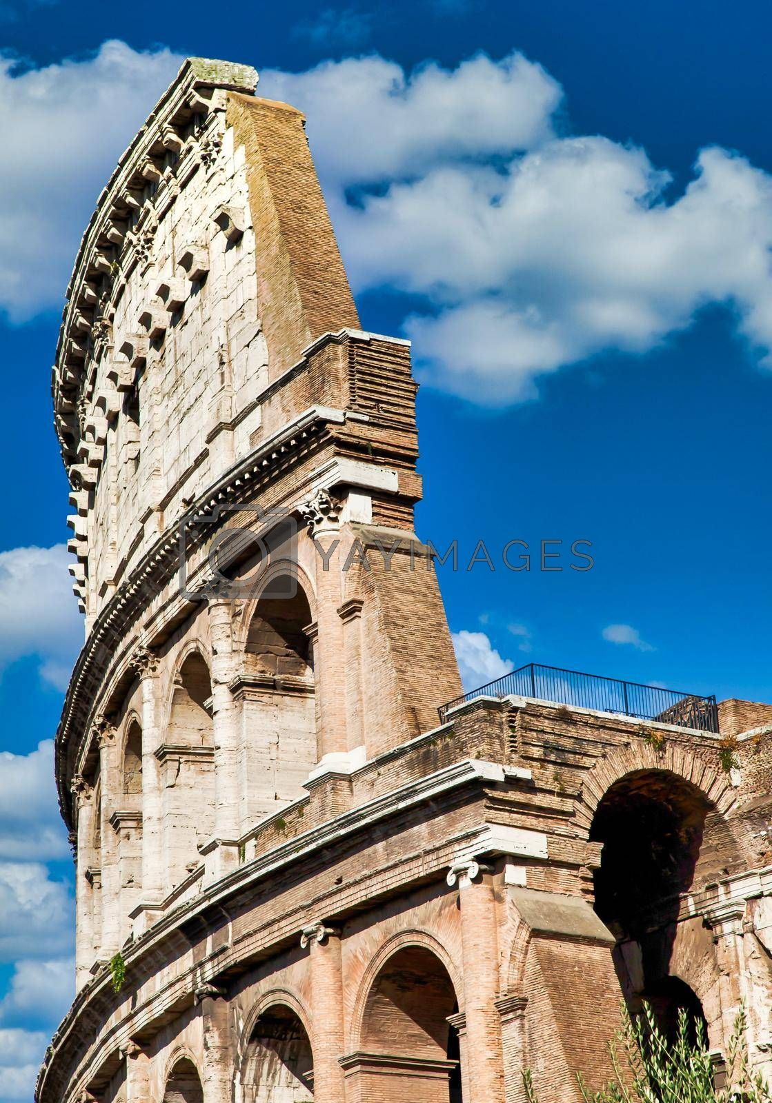 Rome, Italy. Arches archictecture of Colosseum (Colosseo) exterior with blue sky background and clouds.