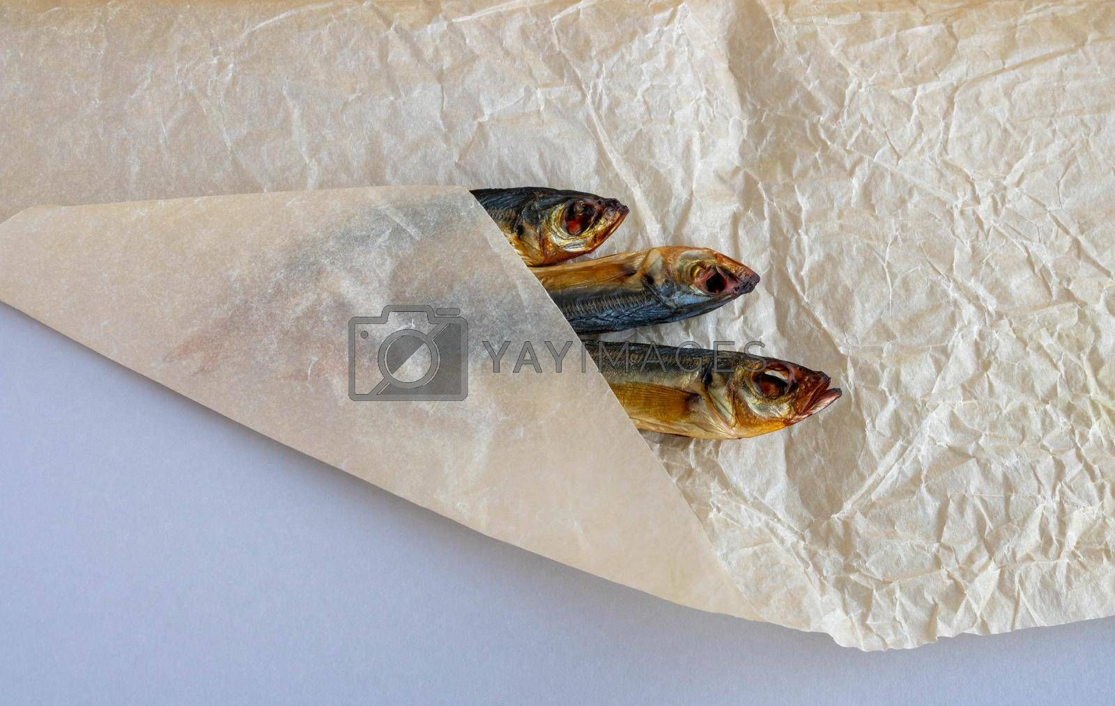 A smoked horse mackerel close-up lies wrapped on a crumpled paper background .
