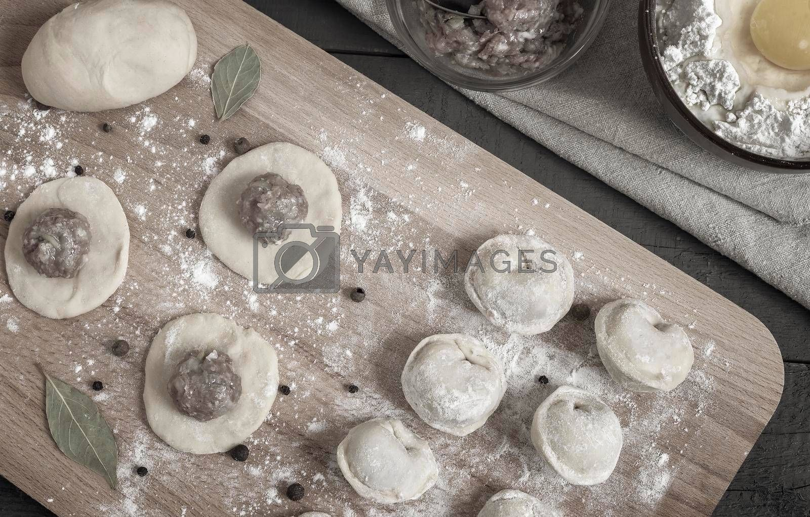 Cooking homemade dumplings, Russian dumplings with meat on a wooden table and ingredients for cooking. Rustic style. Top view with copy space. Flat lay
