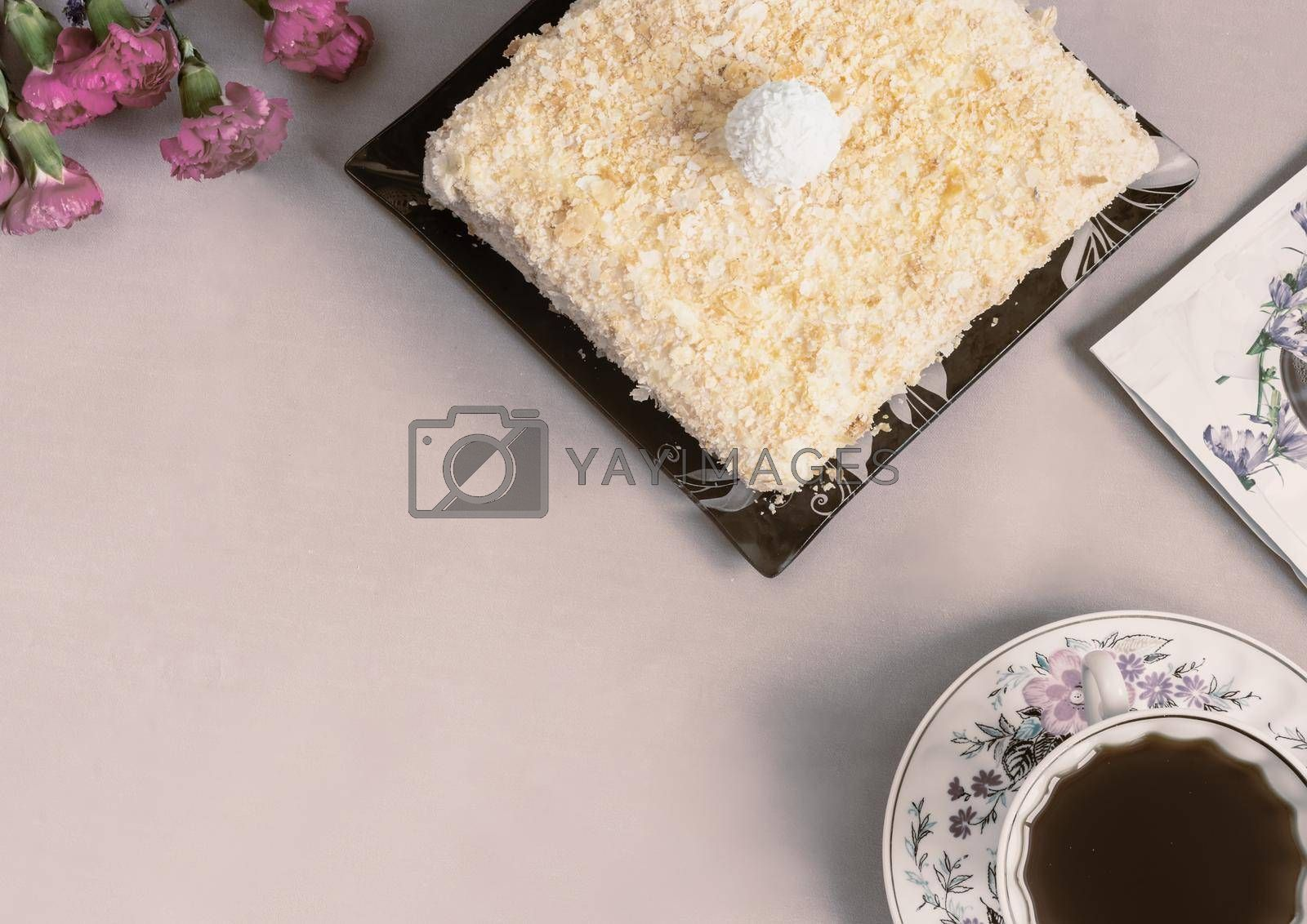 Alternative coffee substitute: a hot decaffeinated drink made from natural chicory, on the table in a white cup. Next to a delicious cake and flowers. Top view with copy space.
