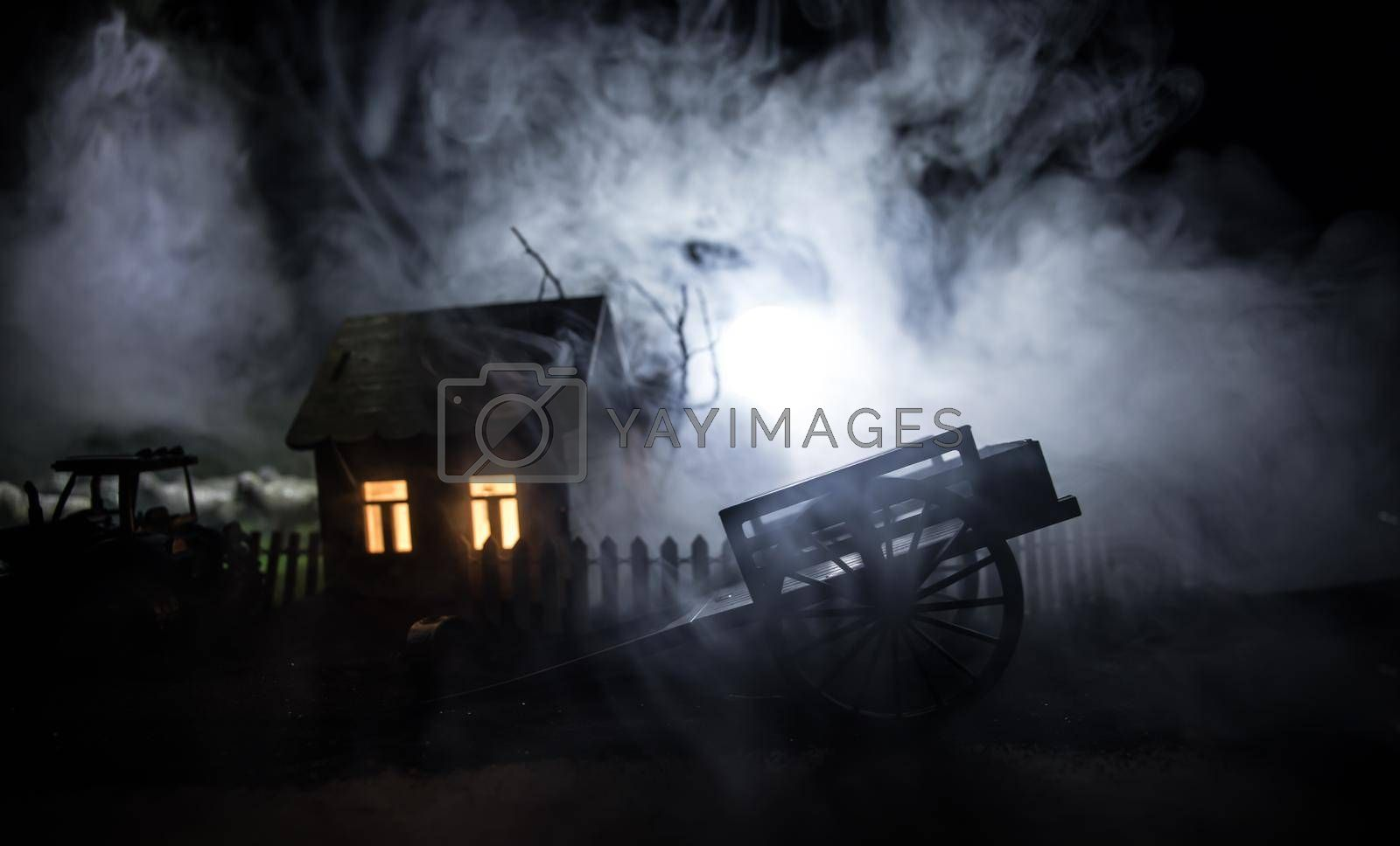 Full moon over quiet village at night. Decorative toy carriage at house with giant green grass under the moonlight. Selective focus