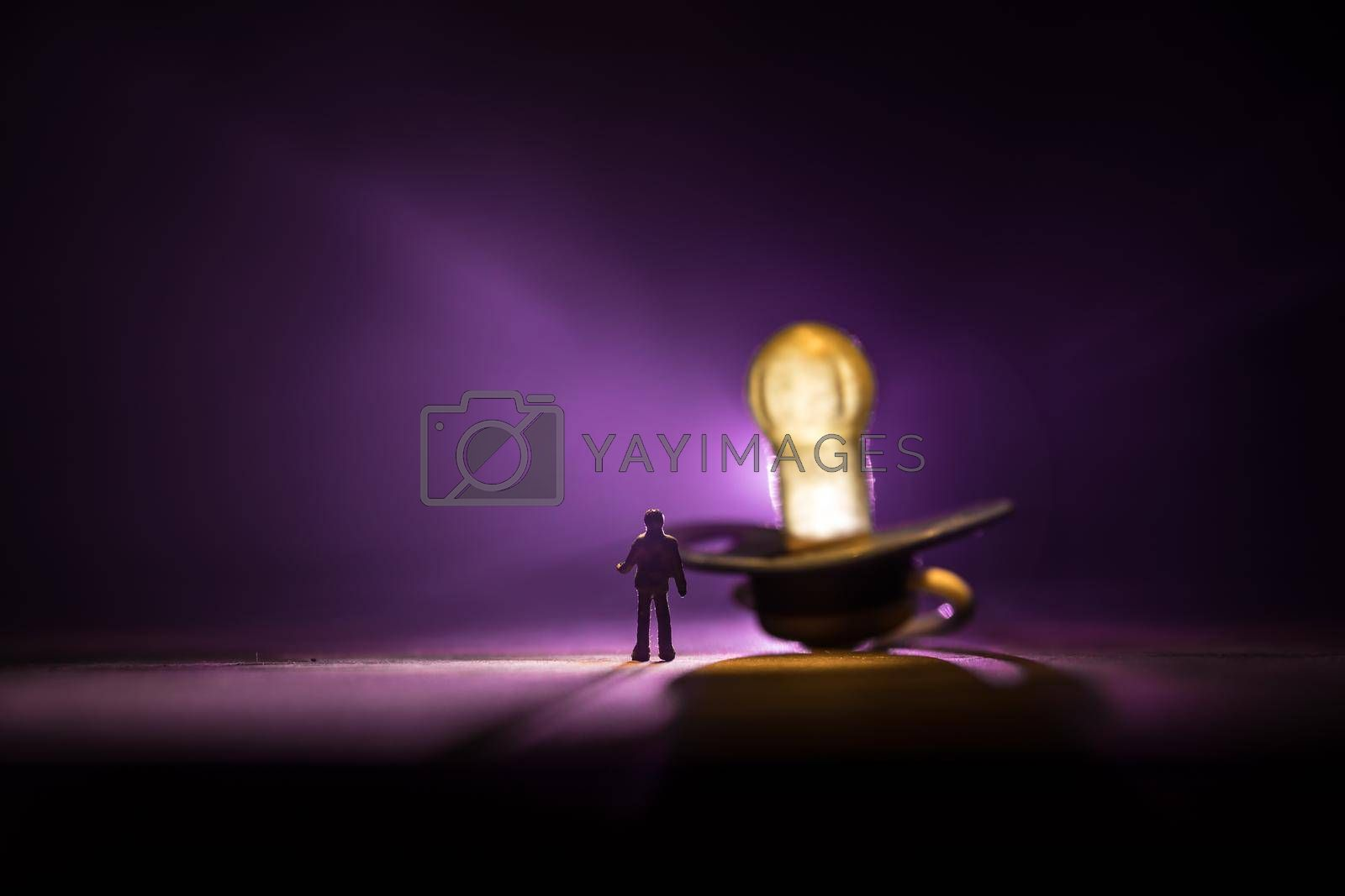 Creative concept. Man silhouette standing at giant baby pacifier on wooden table with low key toned background. Selective focus