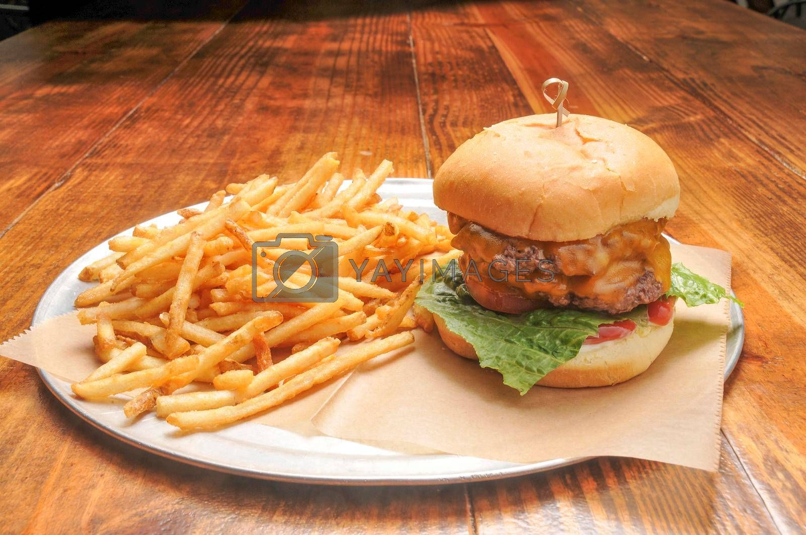 Delicious cheeseburger and an order of French fries.