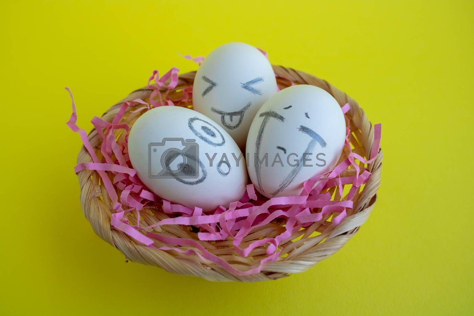 In the basket are three charming white eggs with faces on a yellow background. Easter Concept.