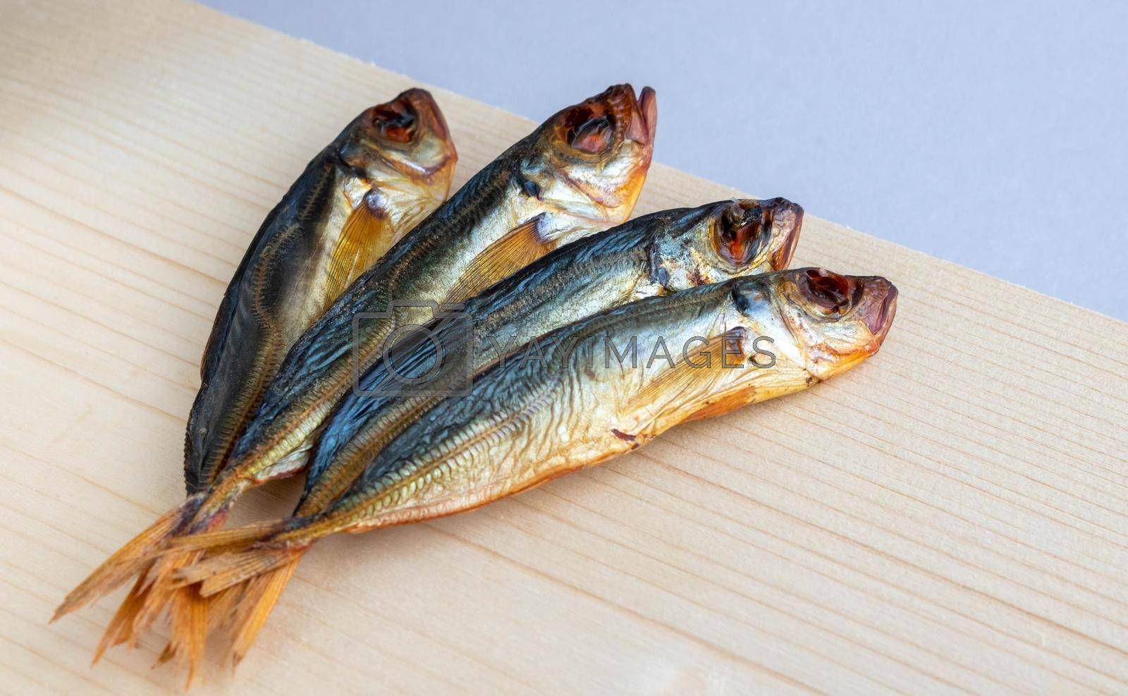 Horse mackerel fish, cold smoked. Smoked fish close-up on a wooden background .Food industry.