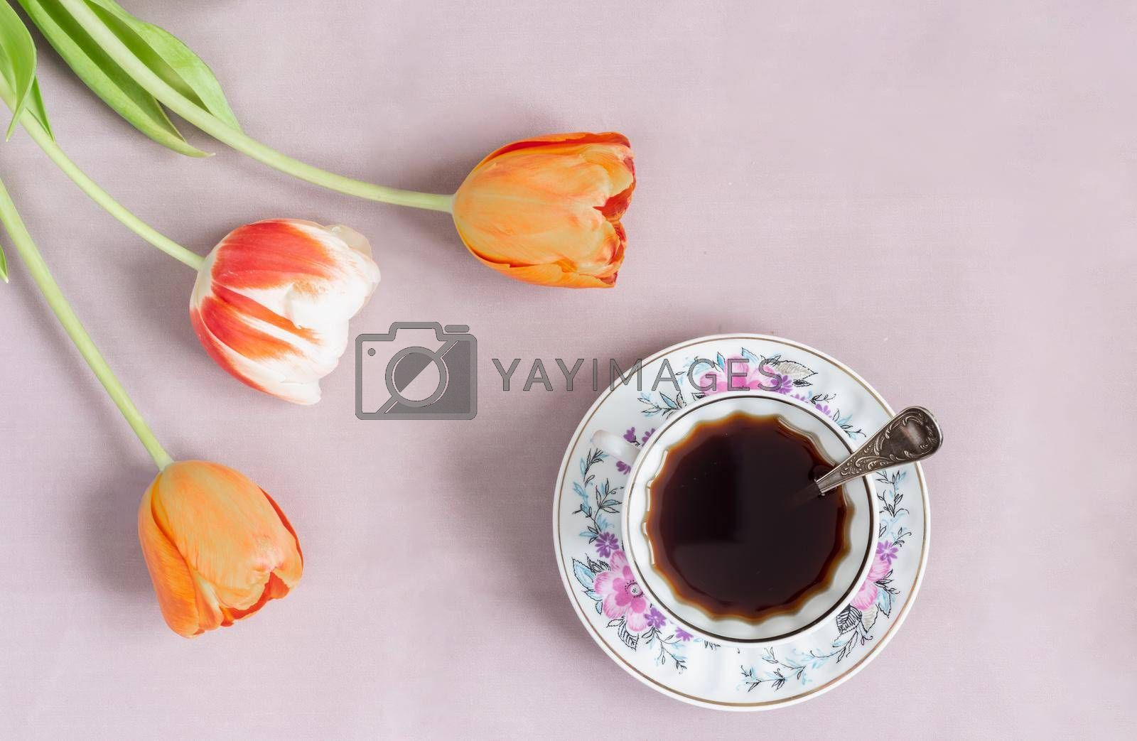 Alternative coffee substitute: a hot decaffeinated drink made from natural chicory, on the table in a white cup. Tulips grow nearby. Top view, copy space