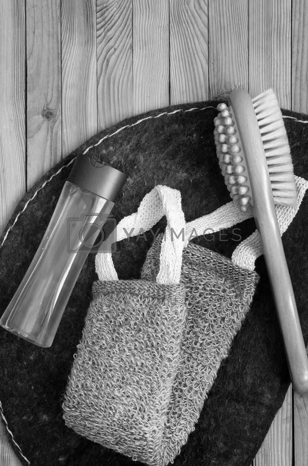 Accessories for visiting a bath or sauna on a wooden background: a washcloth, a mat, a massage brush and shower gel. Top view with copy space. Flat lay