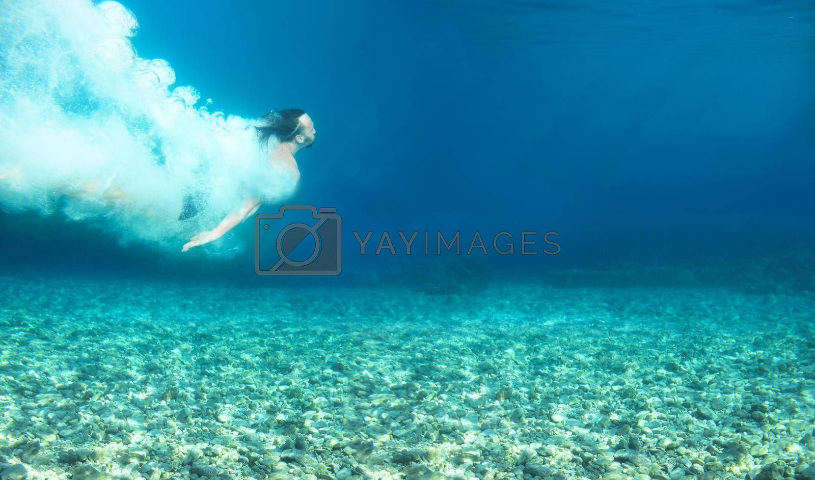 Man swimming under water in blue transparent sea underwater shot copy space for text