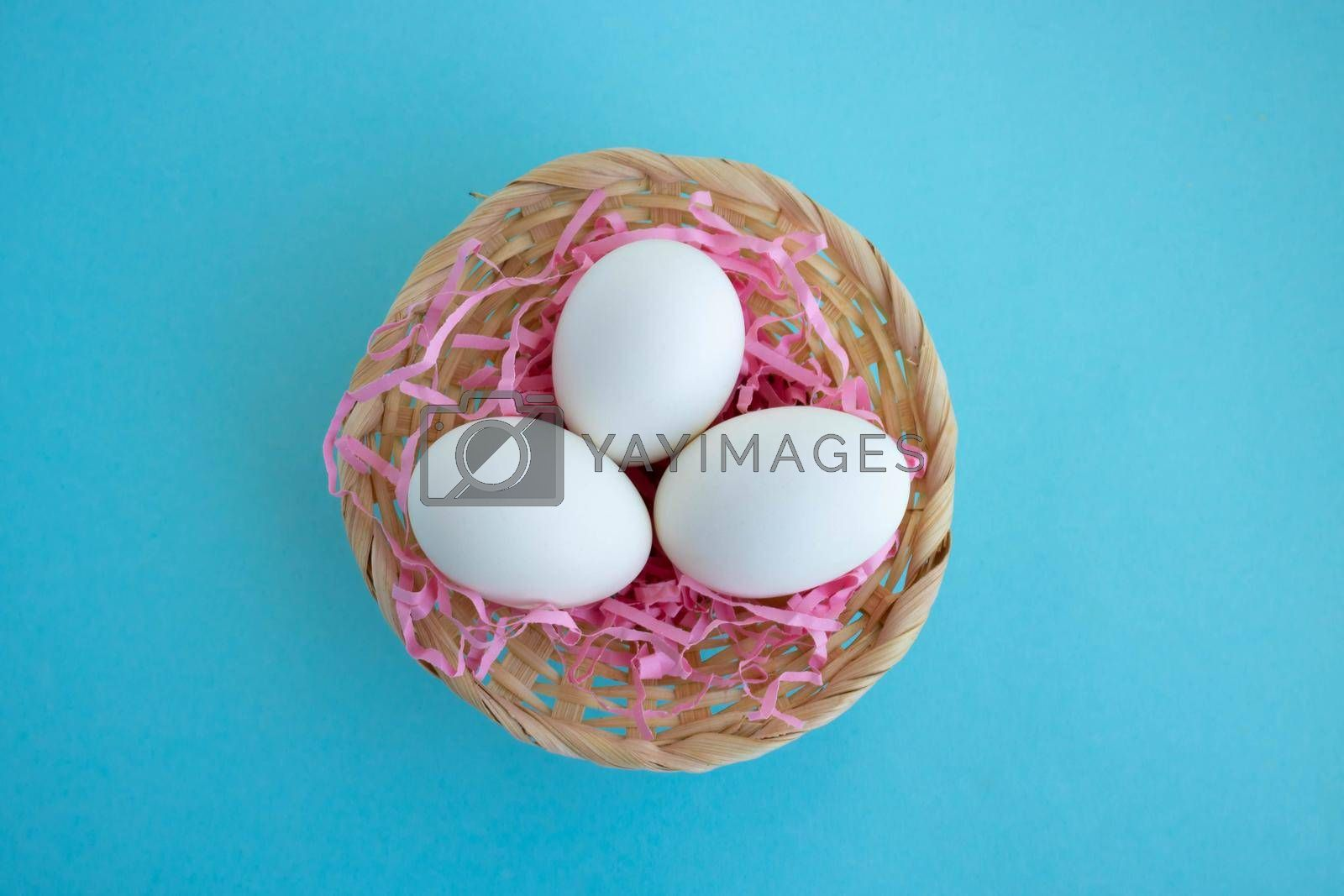 Royalty free image of A basket with white eggs on a blue background. Easter Concept by lapushka62