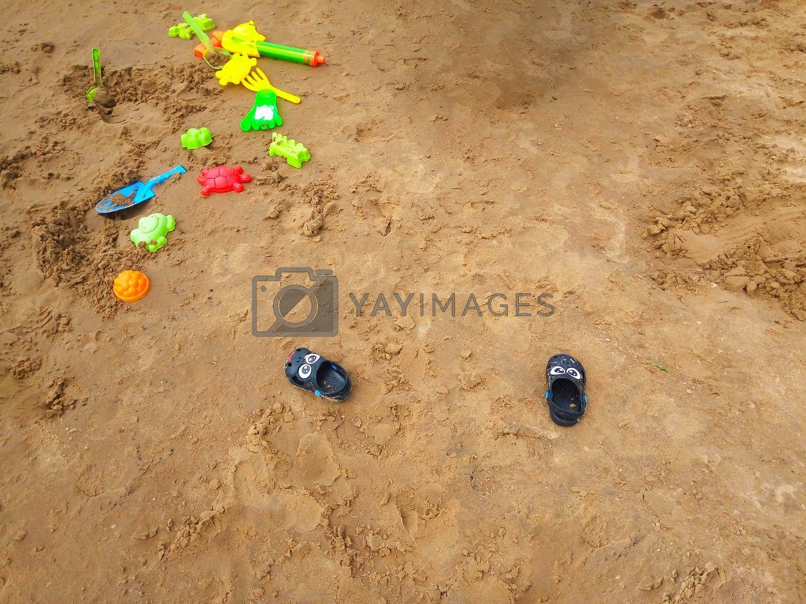Concept of beach recreation for children. Bright plastic children's toys in the sand. Top view. Space for text.