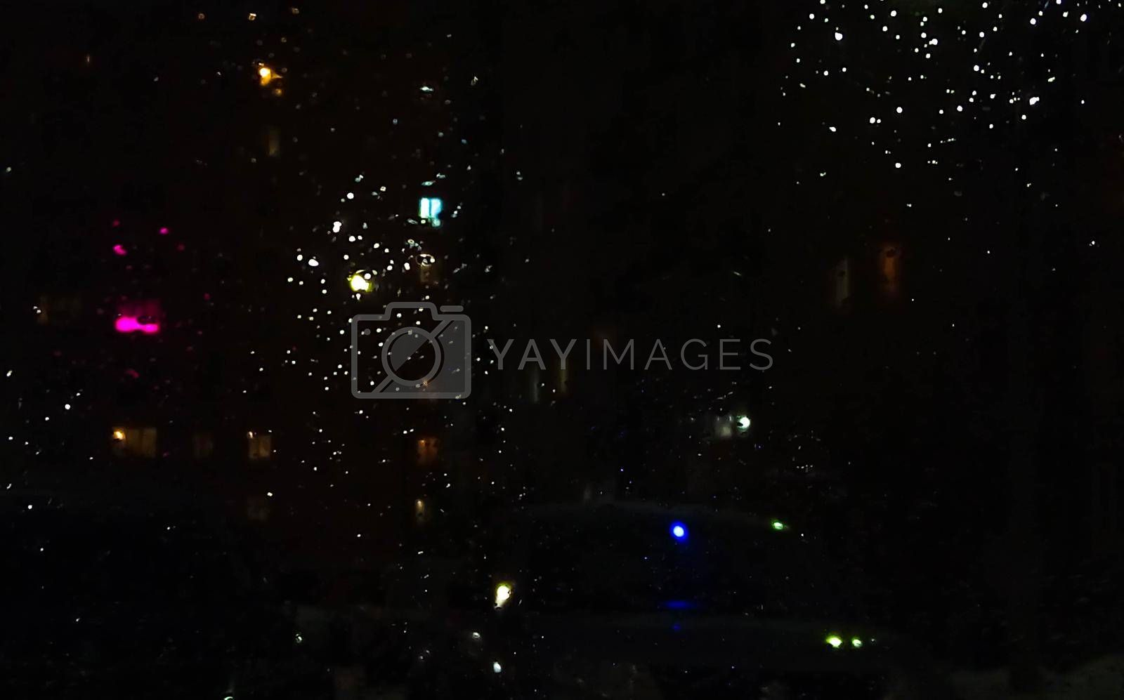 Reflection in a glass of glass. Blurred fires of distant houses. Window.