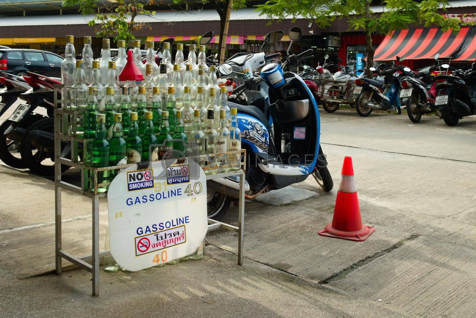 Royalty free image of 2019-11-05 / Phuket, Thailand - Bottles of gasoline for sale in a motorcycle rental stand. by hernan_hyper