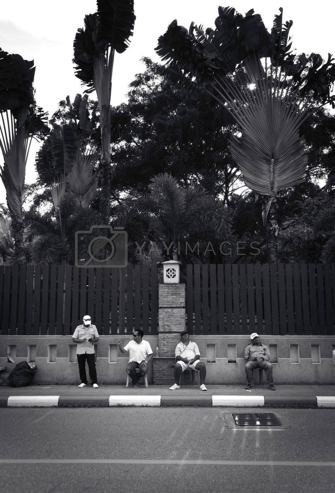 Royalty free image of 2019-11-05 / Phuket, Thailand - Four sitting men idling on the sidewalk. Black and white. by hernan_hyper
