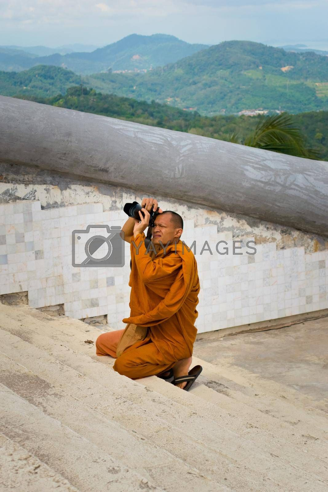 Royalty free image of 2019-11-06 / Phuket, Thailand - A buddhing monk in saffron robes kneels down to take a picture with a DSLR camera. by hernan_hyper