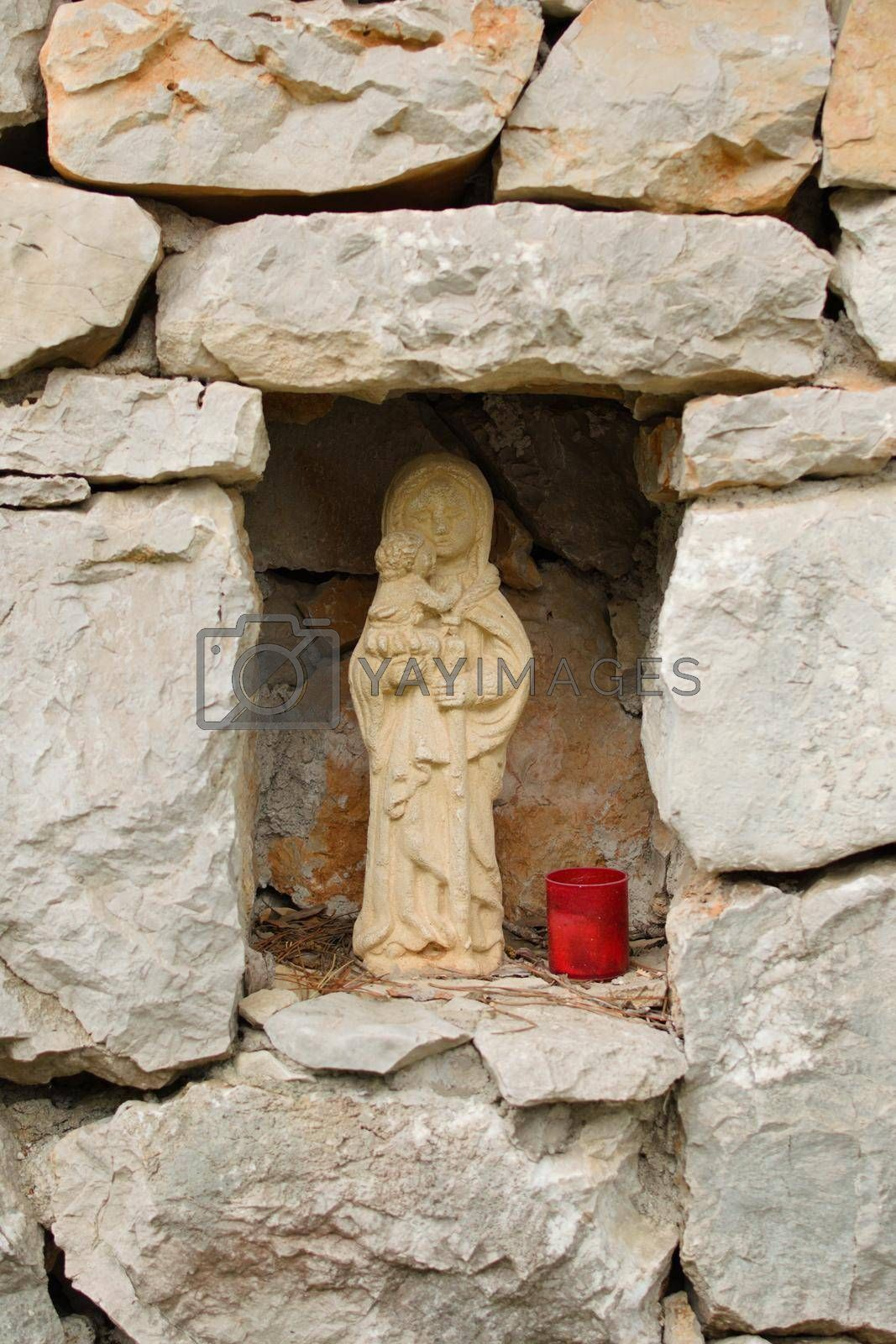 Royalty free image of Small medieval sculpture of Virgin Mary holding a baby Jesus Christ. Early medieval style replica. by hernan_hyper