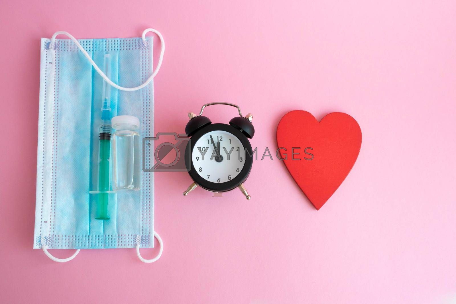 On a pink background-a mask, a syringe, a bottle of vaccine, a watch and a red wooden heart. The concept of medicine and health care.