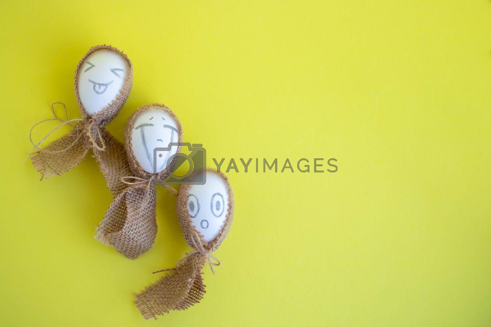 Three white eggs with funny faces in sackcloth on a yellow background. Easter Concept. Space for text by lapushka62