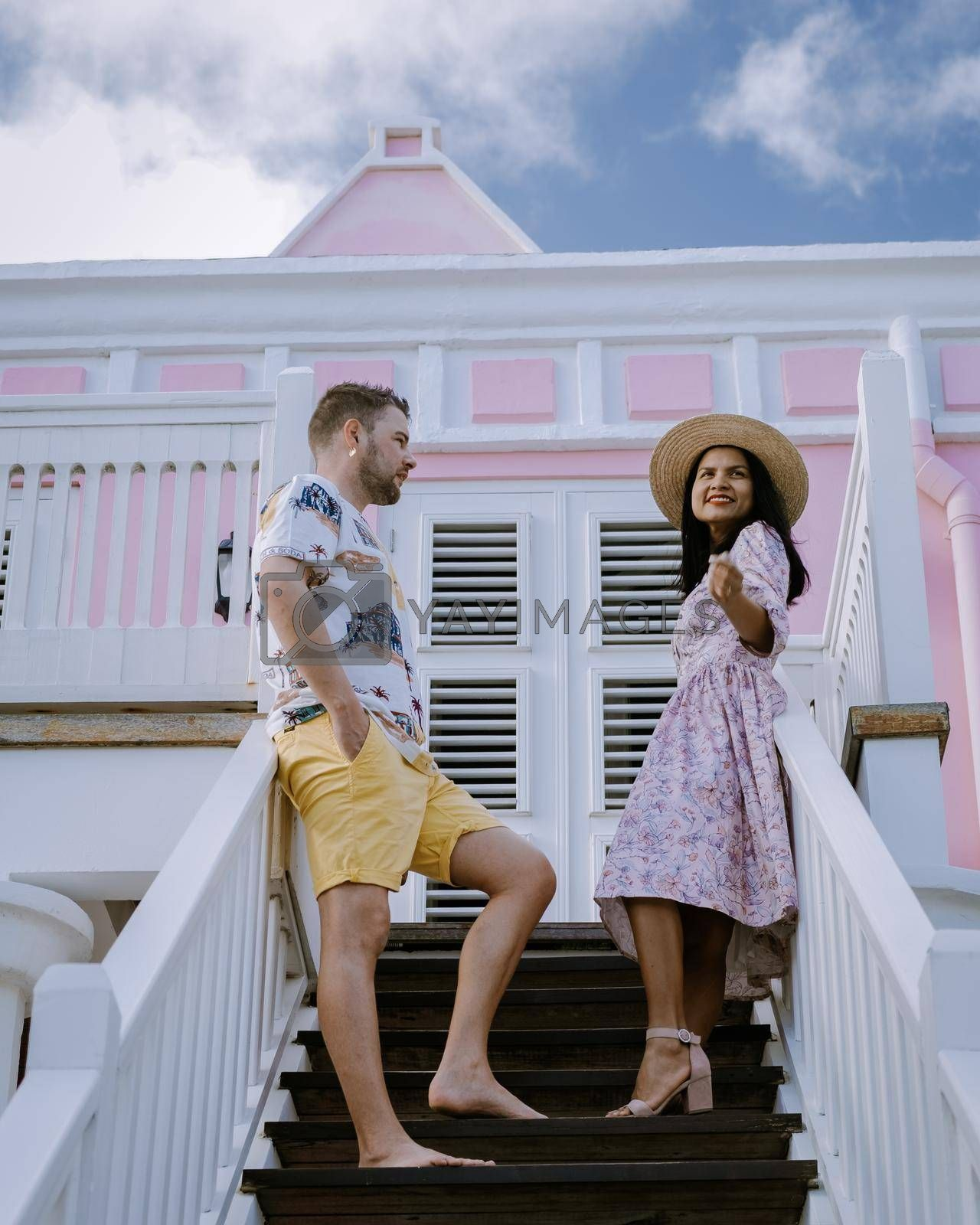Curacao, Netherlands Antilles View of colorful buildings of downtown Willemstad Curacao Colorful restored colonial buildings in Pietermaai, couple men and woman mid age posing by colorful buildings