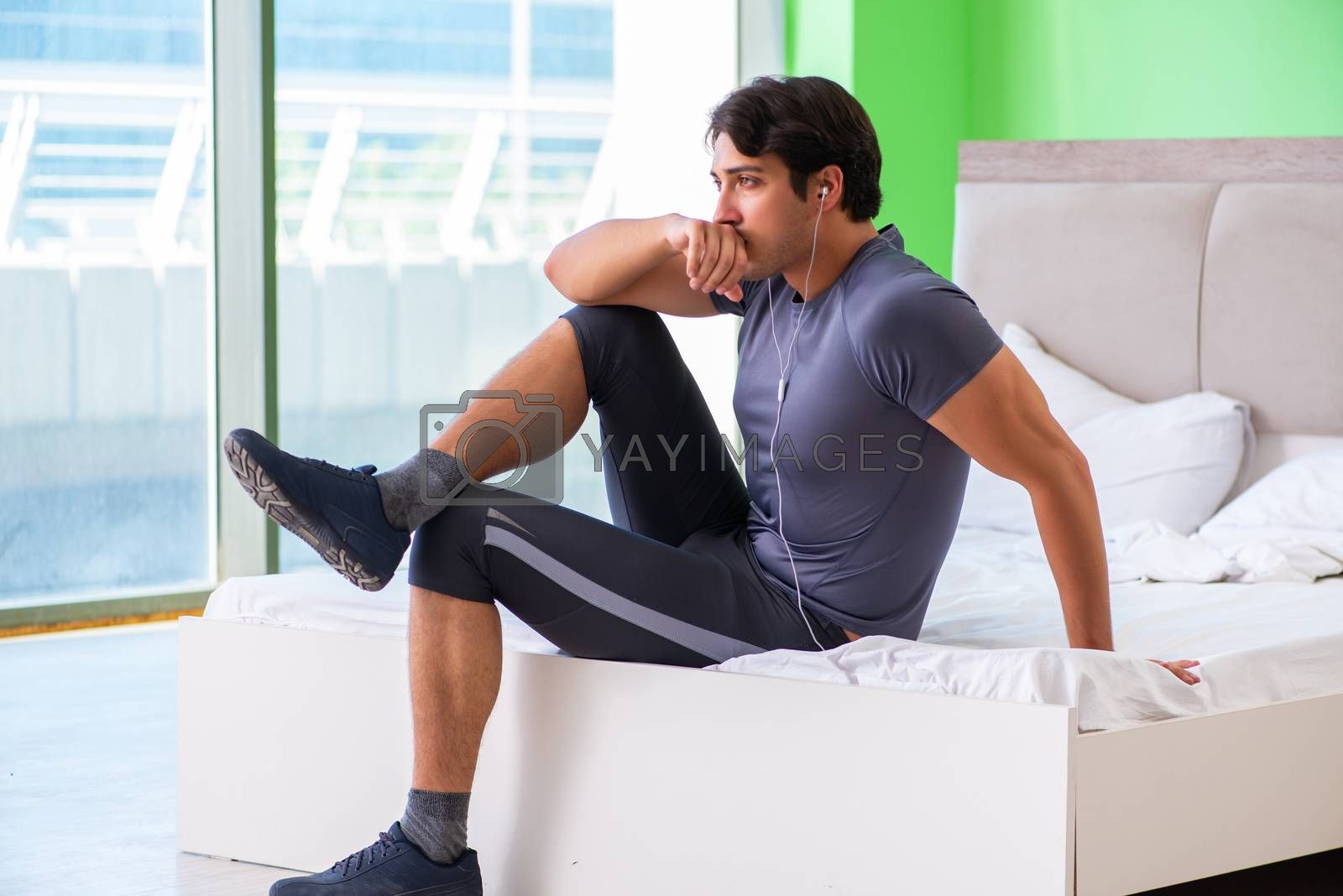 Young handsome man doing morning exercises in the hotel room
