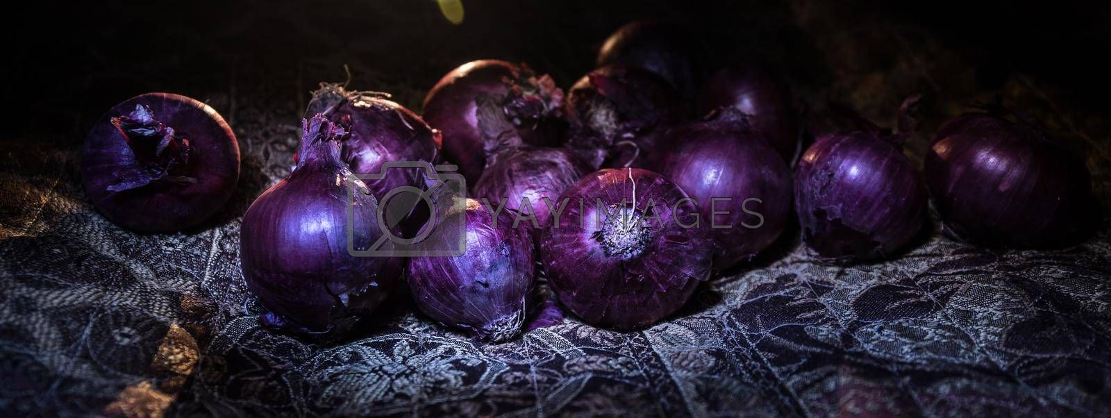 Vegetable concept. Purple onions on carpet surface in dark. Selective focus. Colorful background.