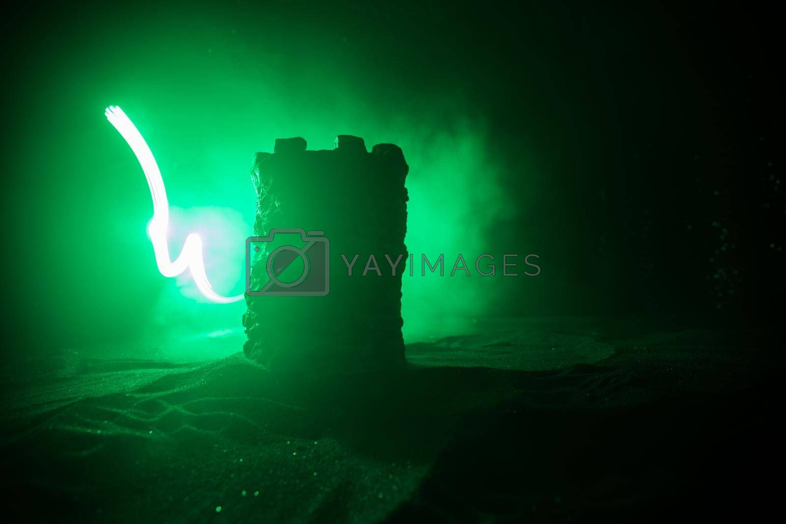 Royalty free image of Stone defence tower at night. Medieval castle miniature with toned foggy backlight. Creative table decoration. by Zeferli