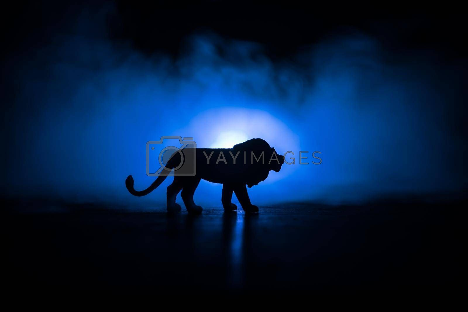 Silhouette of a lion miniature standing on wooden table. Creative decoration with colorful backlight with fog. Selective focus