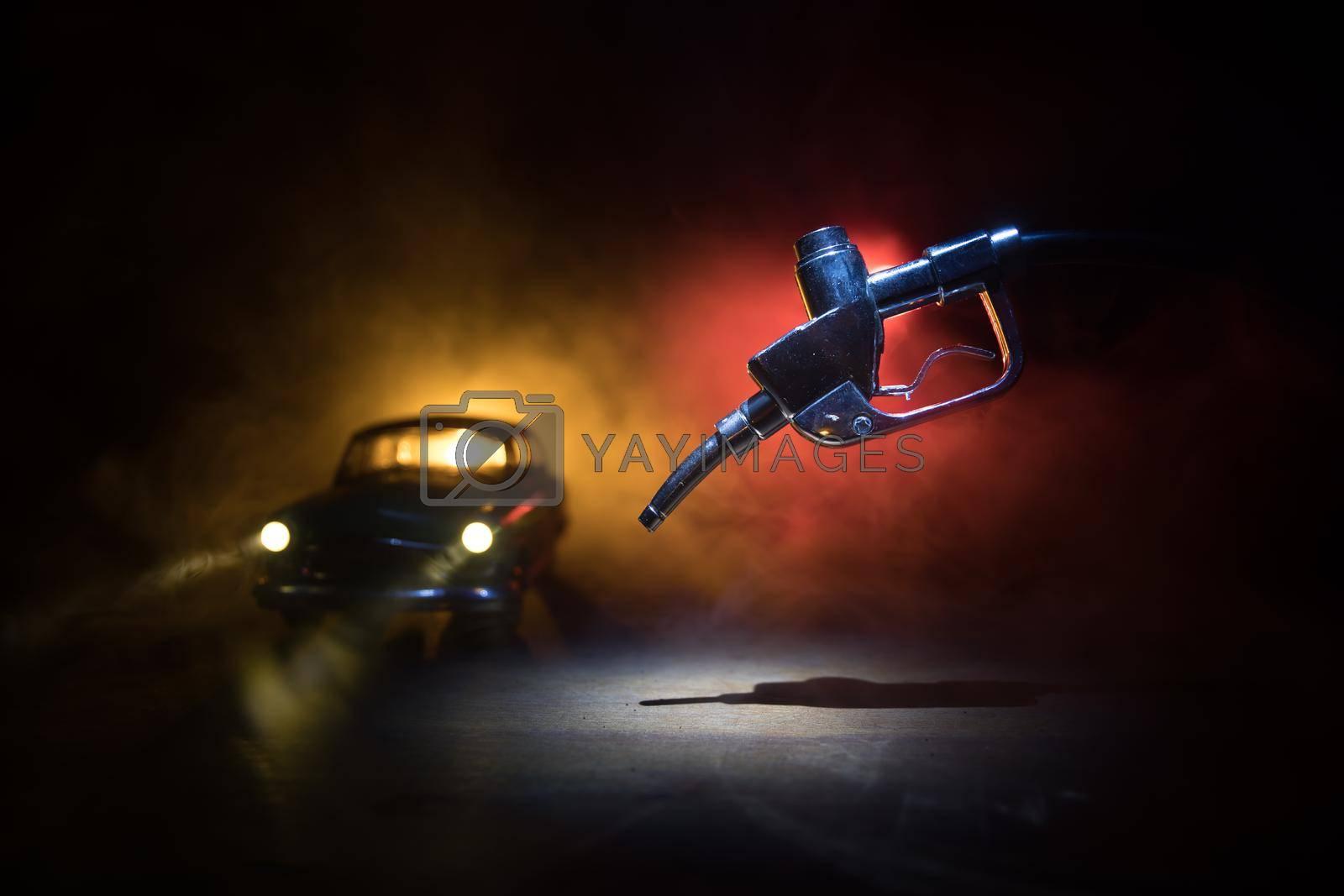 Creative concept. Silhouette of gasoline pistol miniature on dark toned foggy background. Close up. Car miniature on background. Selective focus