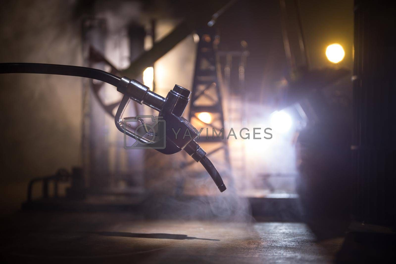 Creative concept. Silhouette of gasoline pistol miniature on dark toned foggy background. Close up. Oil pump and oil refining factory at night with fog and backlight on background. Selective focus