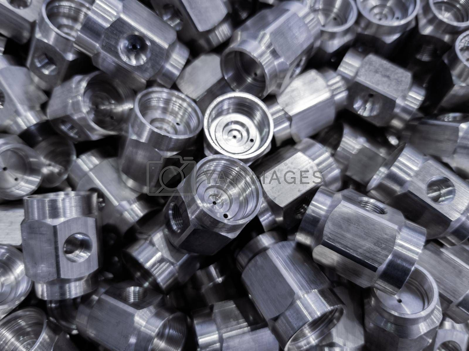 heap of abstract industrial close-up background of shiny steel turned hexagonal parts.