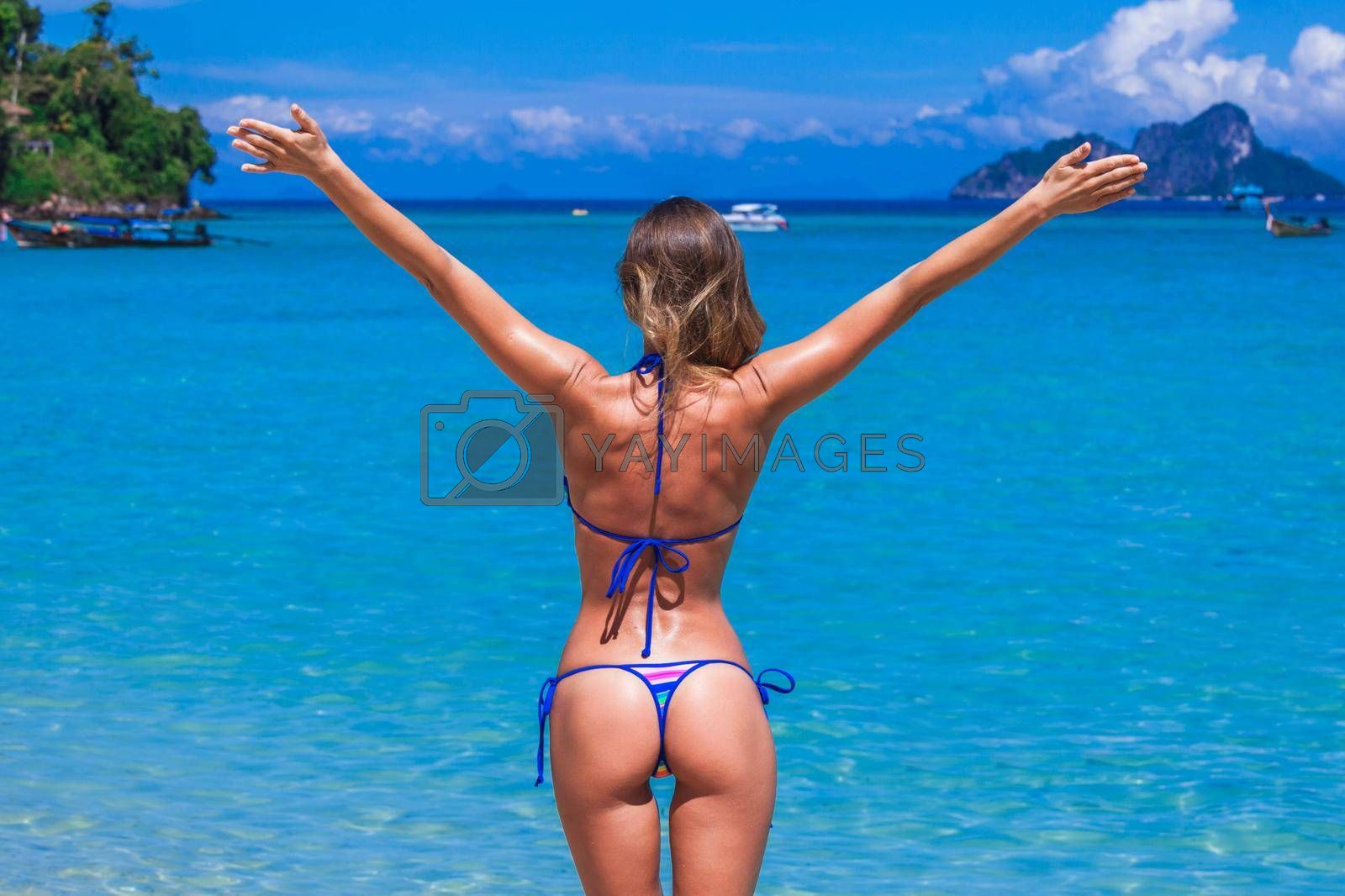 Happy woman with raised hands on beach in Thailand