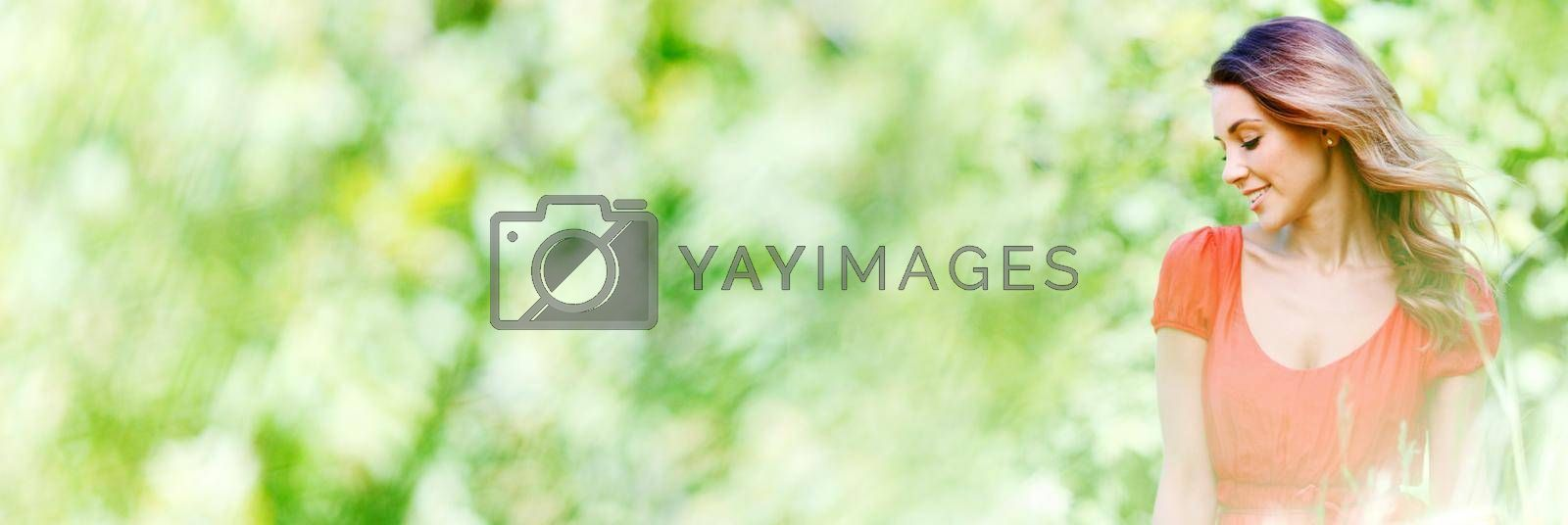 Portrait of young woman in countryside at spring windy day, bokeh background with copy space for text