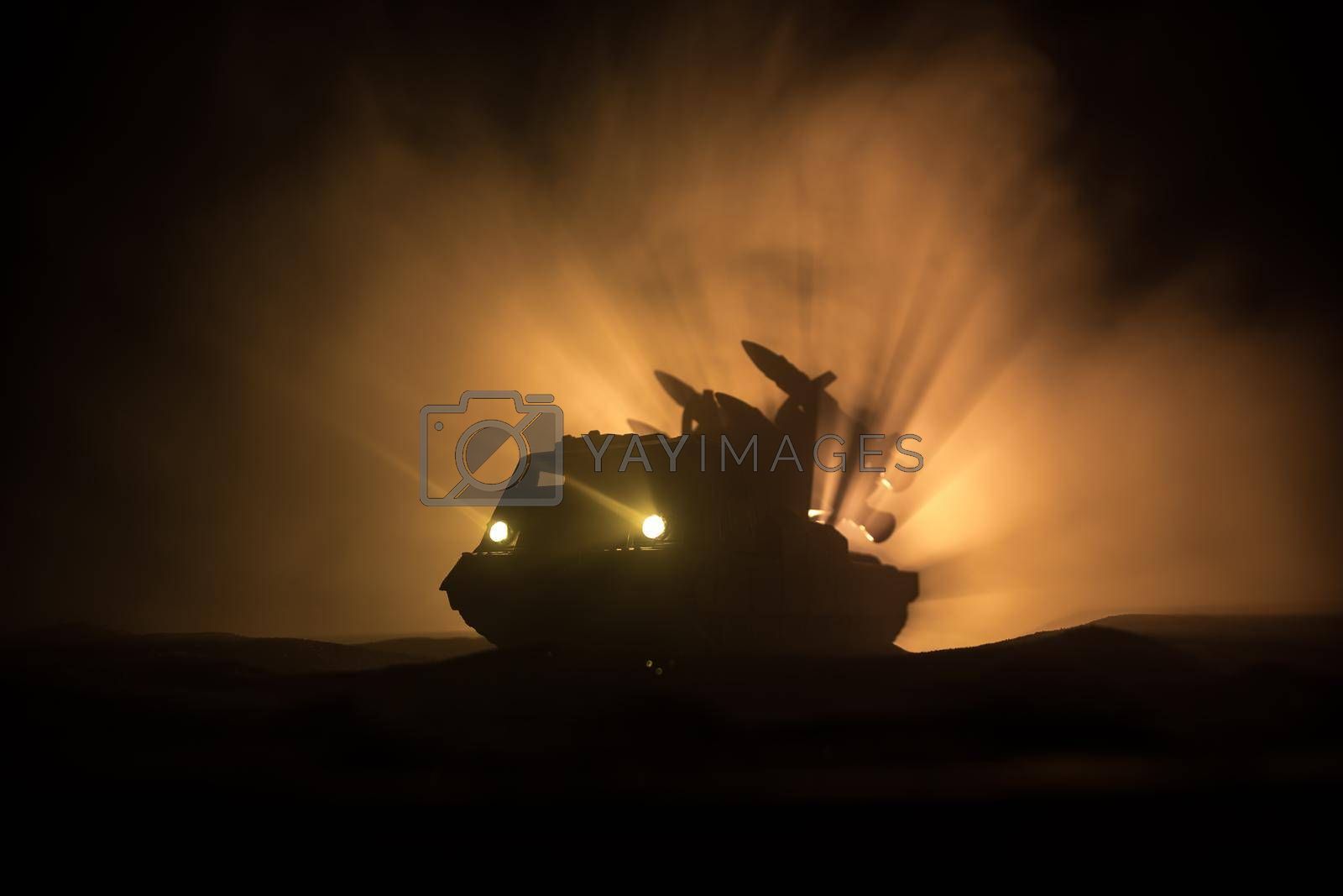 War concept. Battle scene with rocket launcher aimed at gloomy sky at night. Rocket vehicle ready to attack on cloudy war Background. Selective focus
