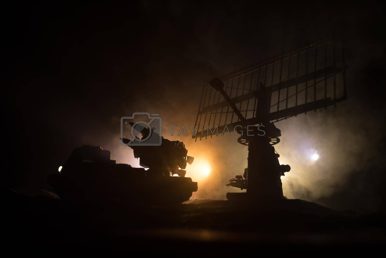 Creative artwork decoration. Silhouette of mobile air defence truck with radar antenna at night. Rocket launcher aimed at sky ready to attack. Selective focus