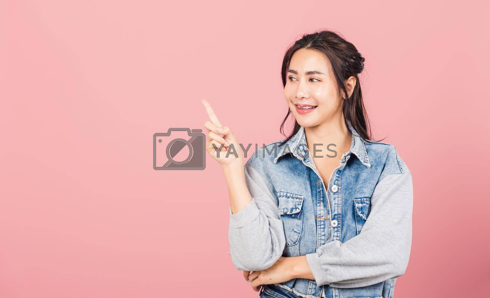 Happy Asian portrait beautiful cute young woman standing smiling indicate finger empty space looking to space, studio shot isolated on pink background, Thai female pointing index out with copy space