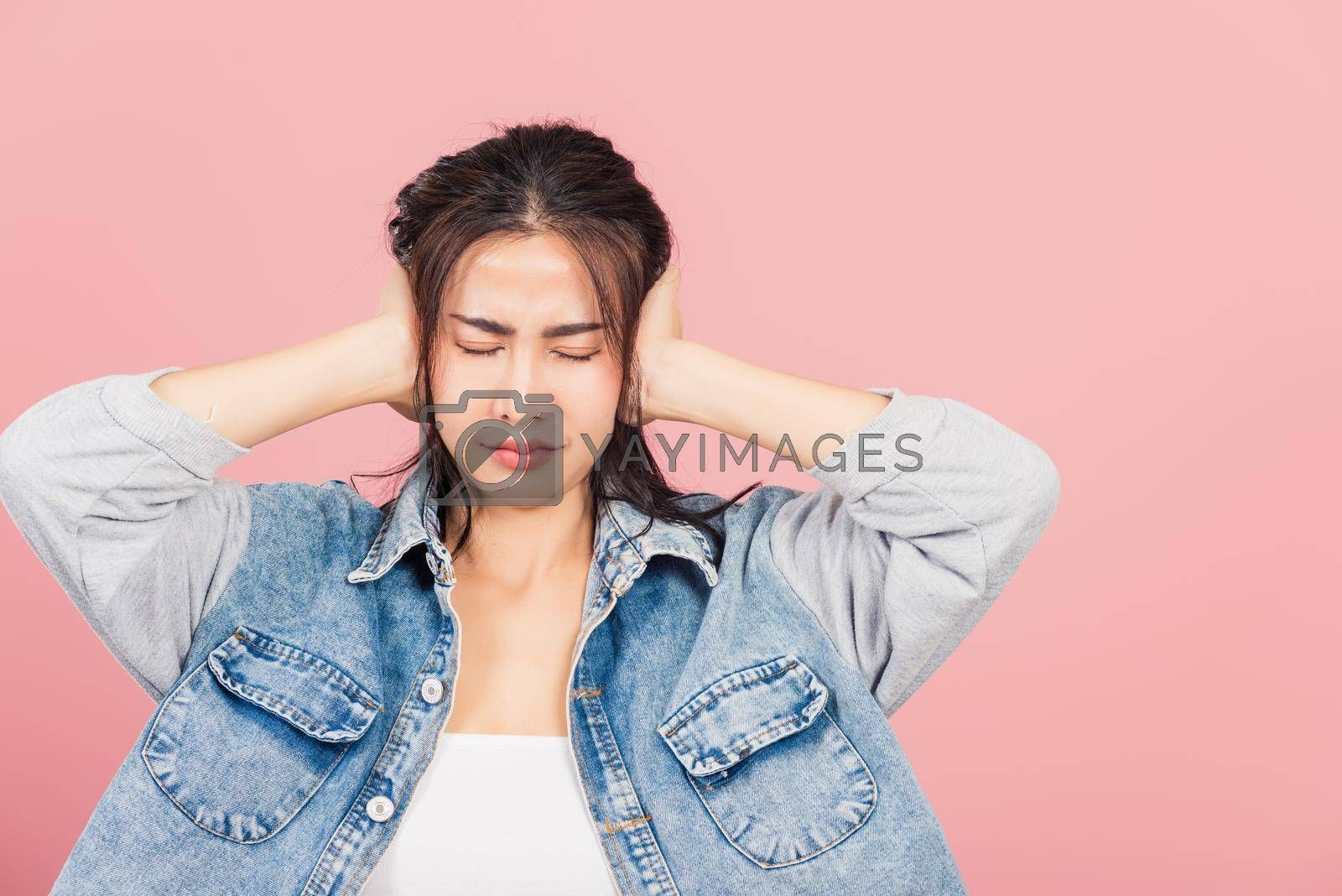 Asian portrait beautiful cute young woman wear denim have closed ears with hand palms and close eyes, studio shot isolated on pink background, Thai female covers ears for loud noise with copy space