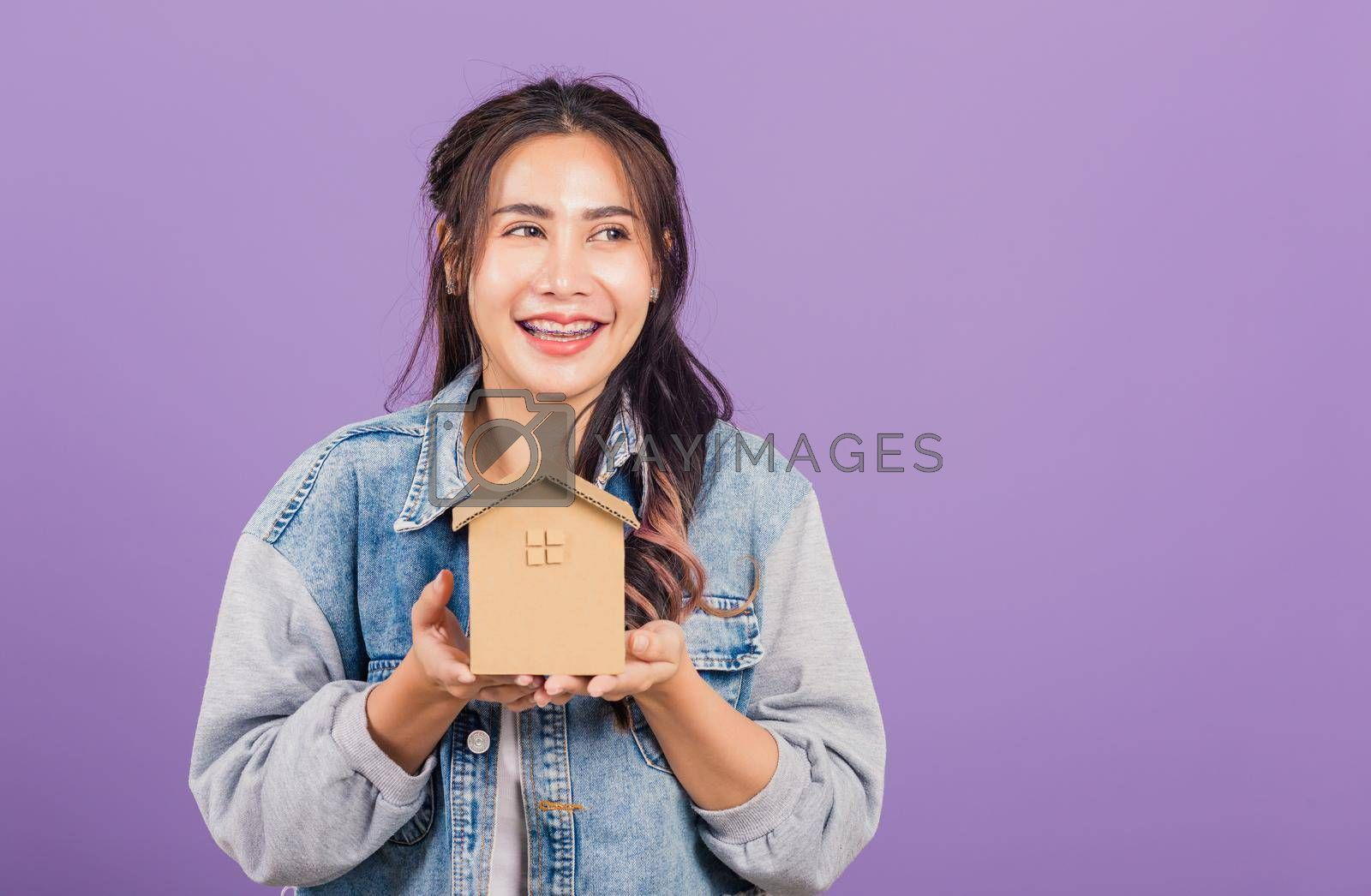 Happy Asian portrait beautiful cute young woman wear denim excited smiling holding house model on hand, studio shot isolated on purple background, broker female hold home real estate insurance