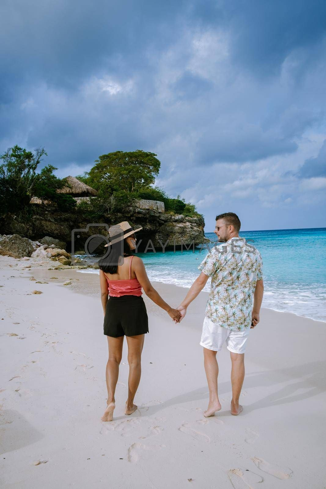 Grote knip beach Curacao, Island beach of Curacao in the Caribbean men and woman on vacation visit the beach. couple mid age men and woman on the beach Playa Knip