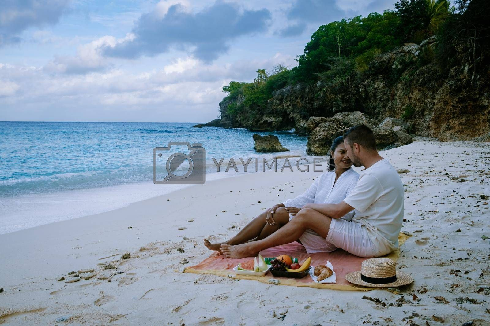 Beach and Pier at playa Kalki in Curacao,picknick on the beach. couple men and woman picknick on the beach