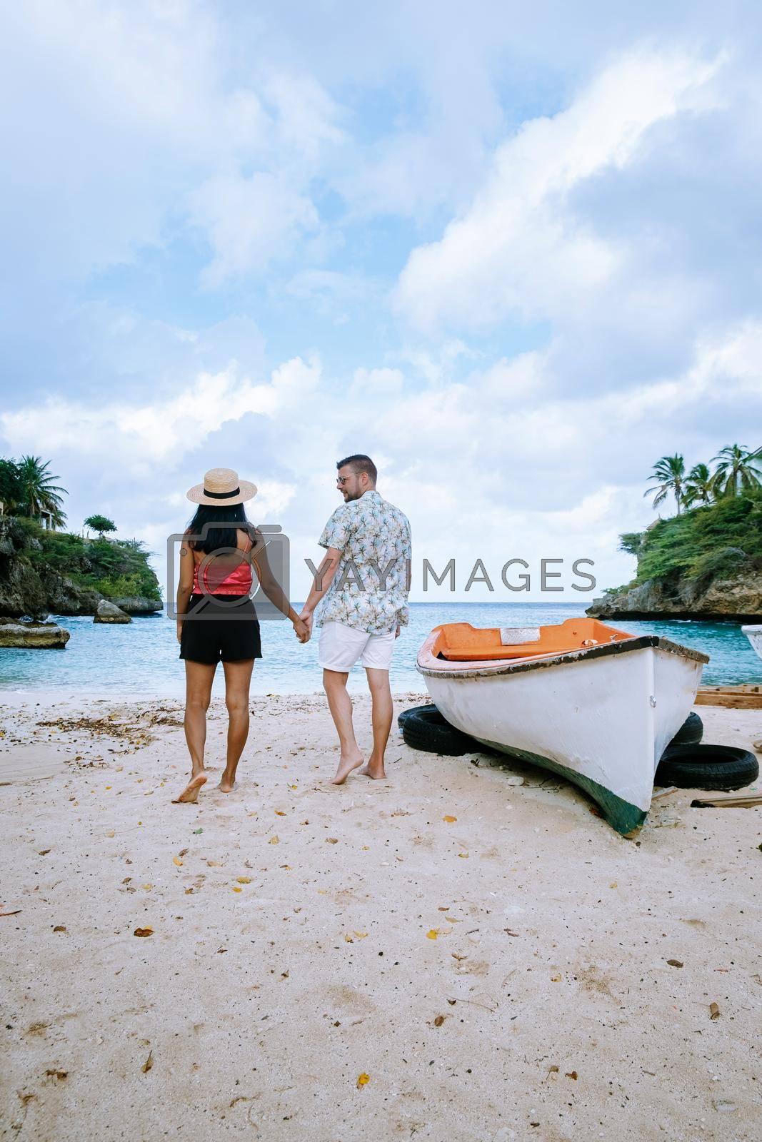 Playa Lagun Beach Cliff Curacao, beautiful tropical bay with white sand and blue ocean Curacao Caribbean, men and woman mid age couple on tropical beach