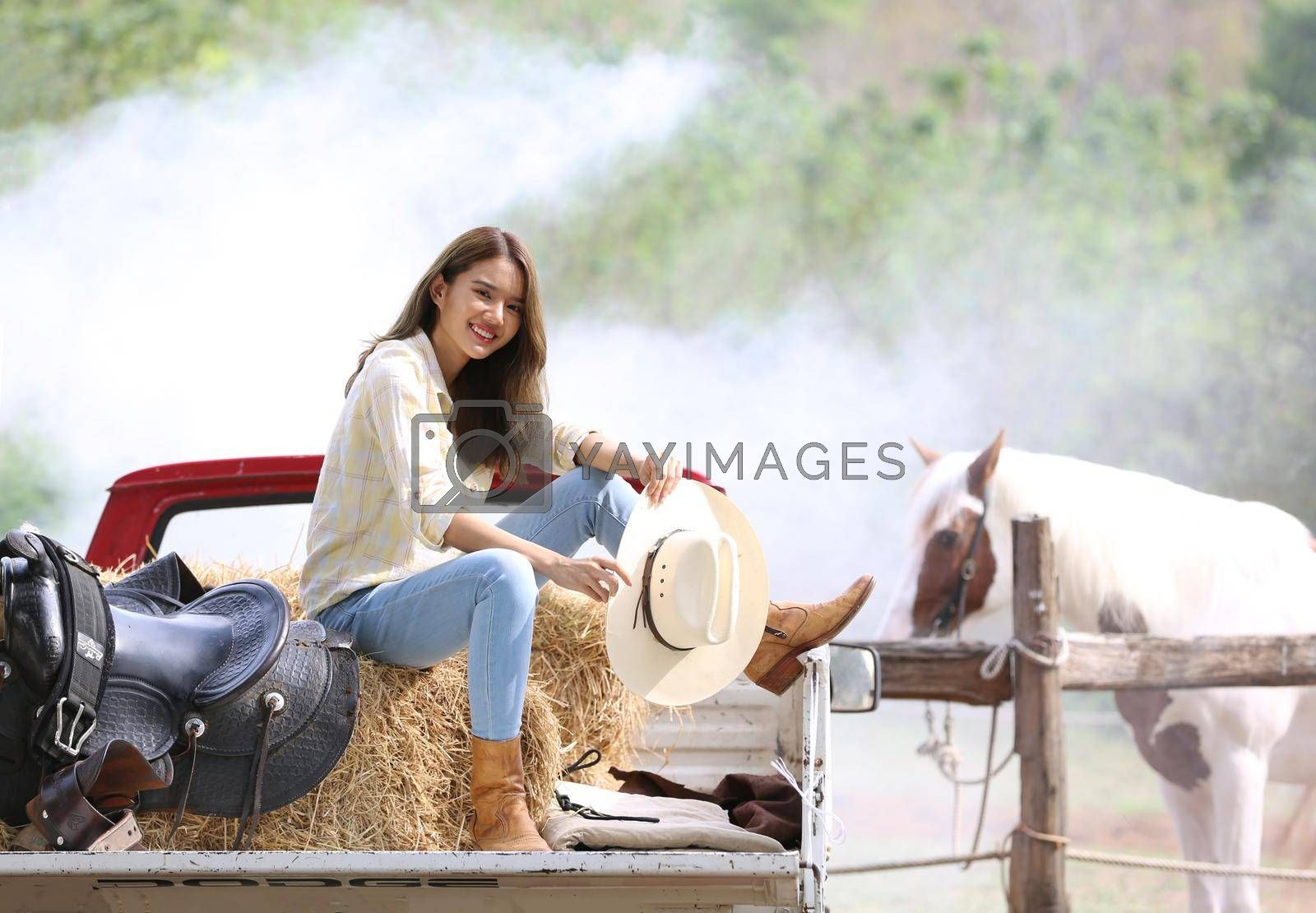 A woman in a cowgirl style sits in a horse ranch with a western farm environment.