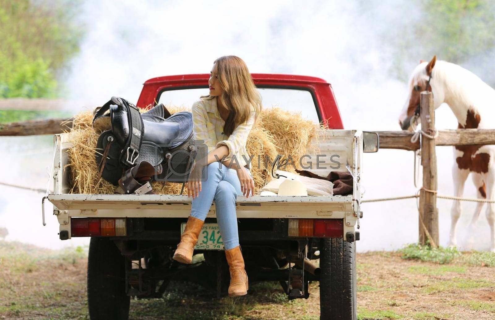 Royalty free image of A woman in a cowgirl style sits in a horse ranch with a western farm environment. by chuanchai