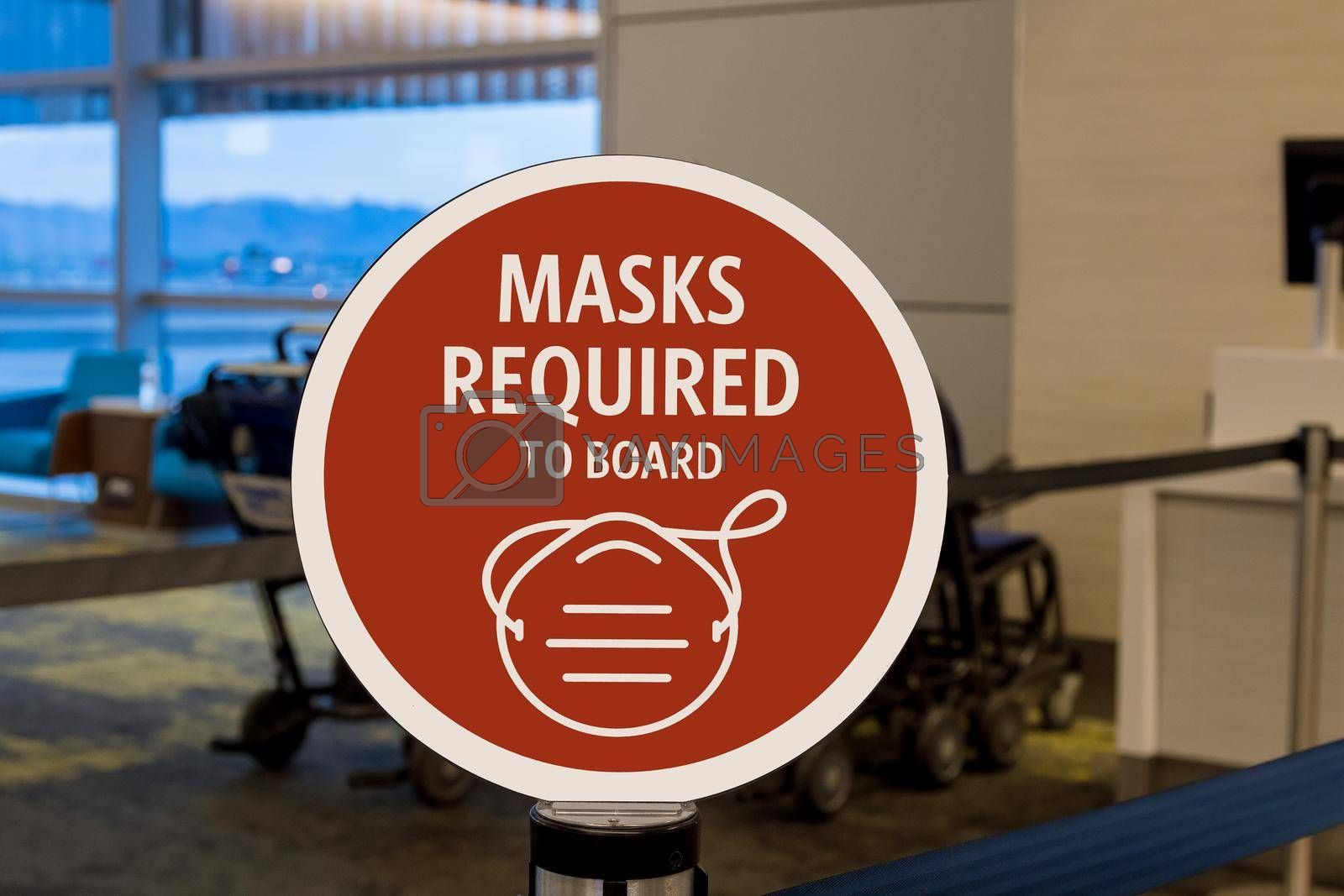 Preventive signs for COVID-19 pandemic before entering a airport terminal on signs in the masks required to board