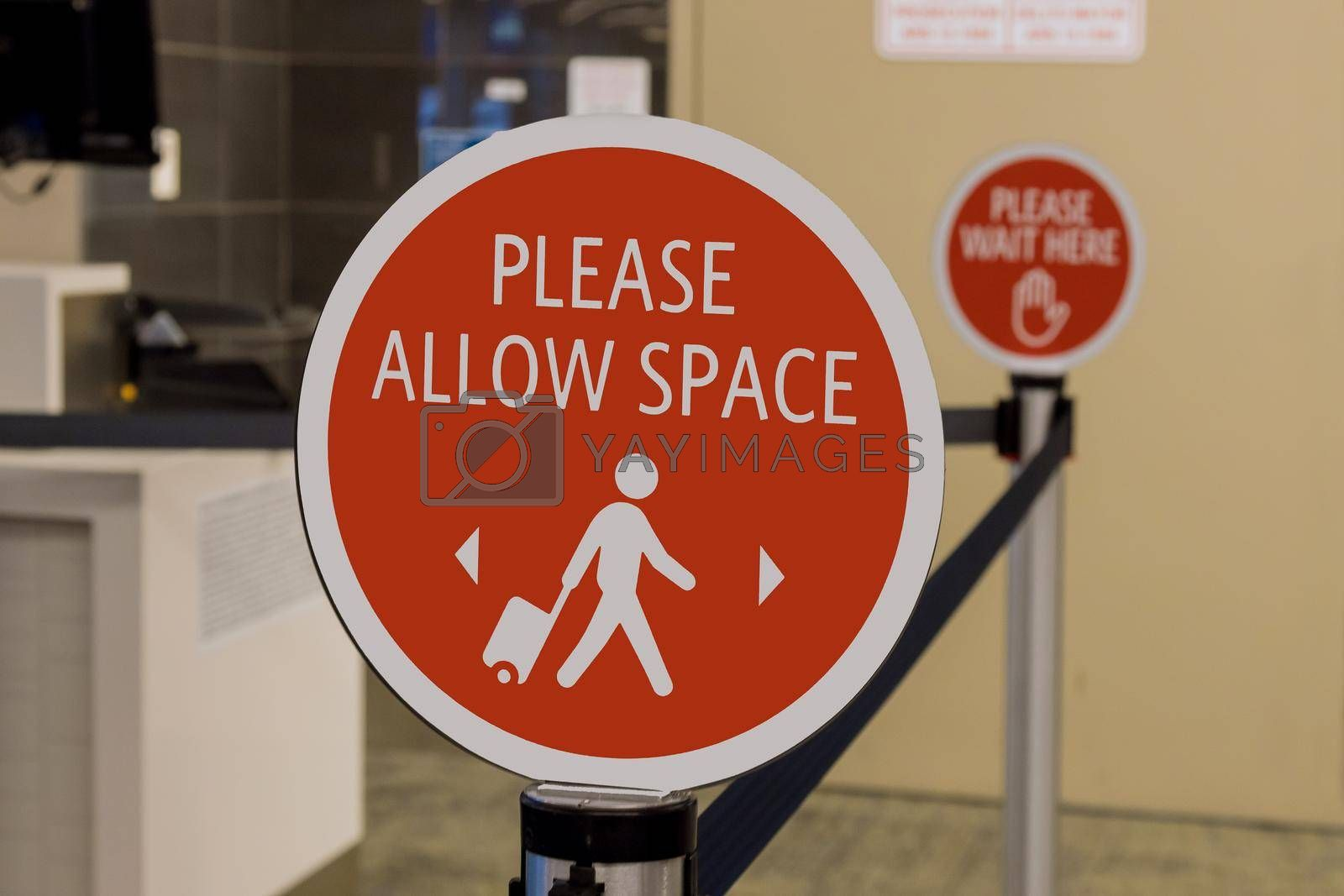 Preventive signs for COVID-19 pandemic before entering a airport terminal on signs in the Please Allow Space airport lounge