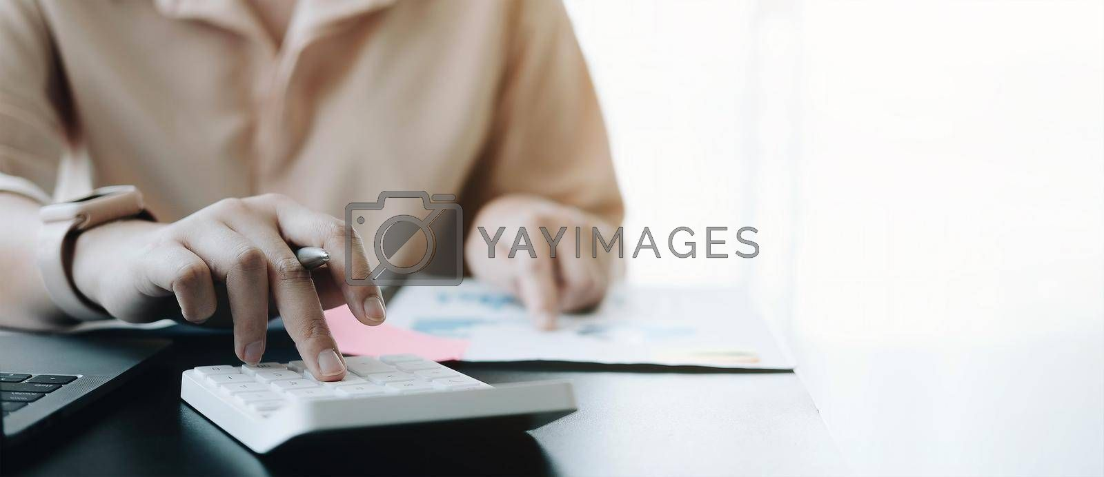 Close up Business woman using calculator and laptop for do math finance on wooden desk in office and business working background, tax, accounting, statistics and analytic research concept.