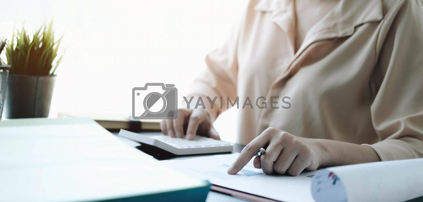 Close up Business woman using calculator and laptop for do math finance on wooden desk in office and business working background tax accounting statistics